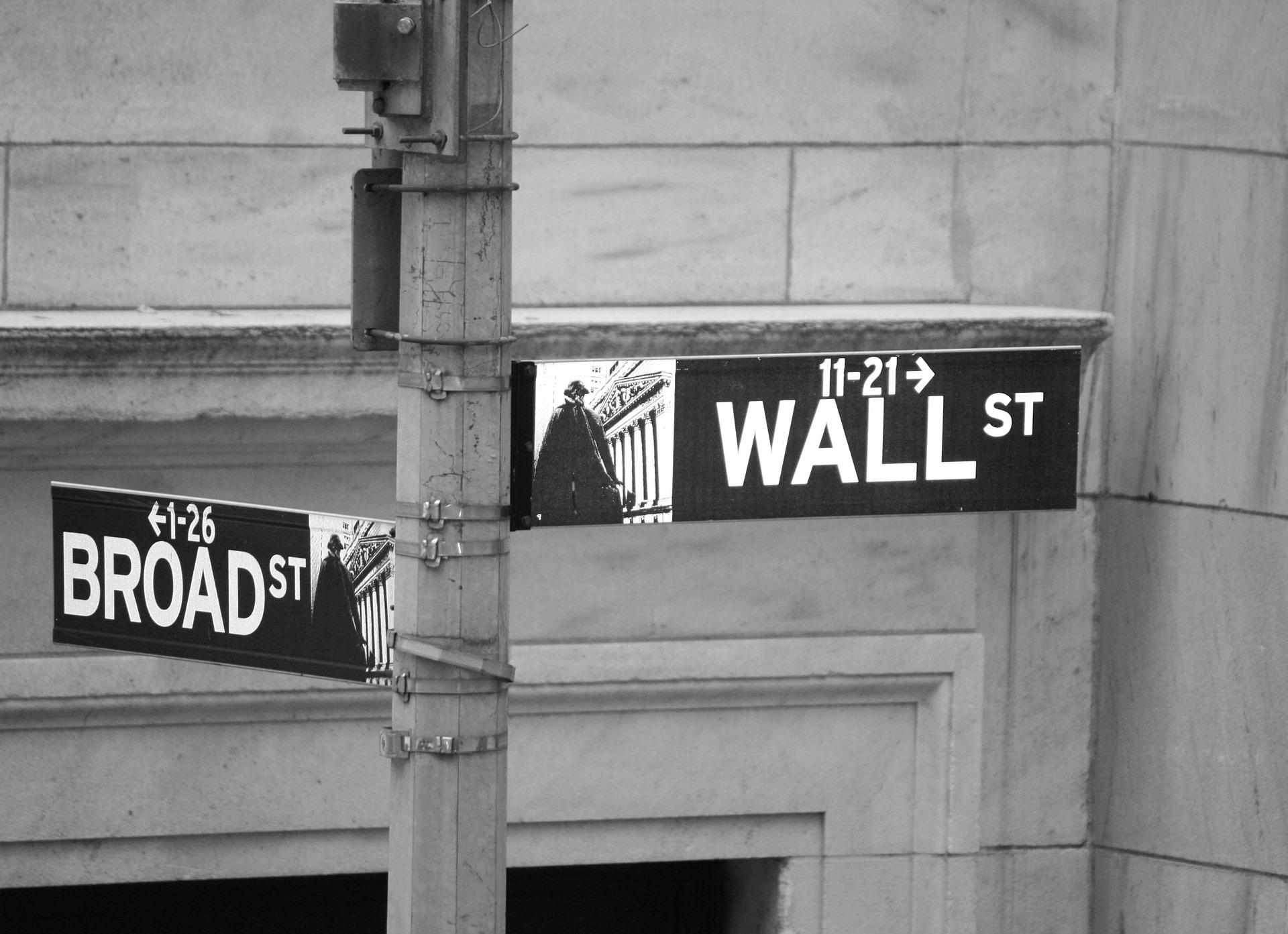 Ein Straßenschild an der Wall Street weist den Weg